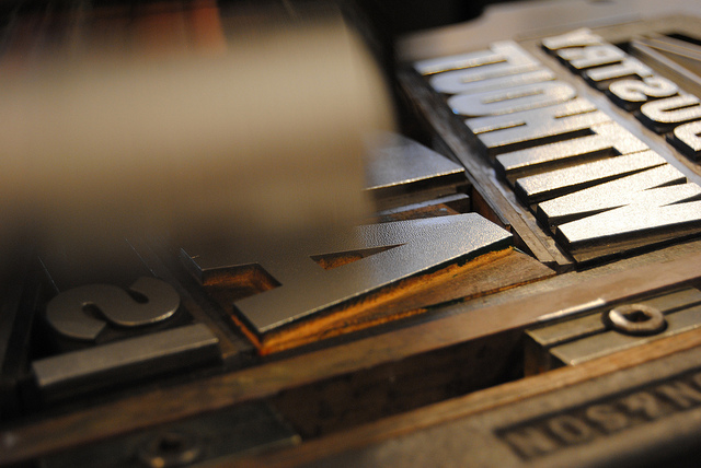 Hand inking wood type for 'Industry Without Art' letterpress print